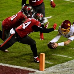 Jan 9, 2021; Landover, Maryland, USA; Washington Football Team quarterback Taylor Heinicke (4) scores a touchdown against the Tampa Bay Buccaneers during the third quarter at FedExField. Mandatory Credit: Brad Mills-USA TODAY Sports
